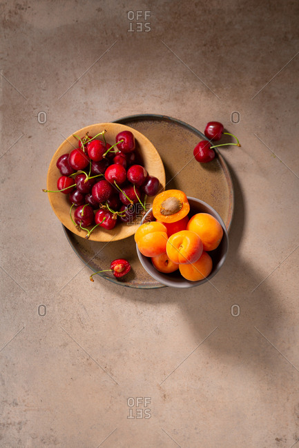 Top view of cherries and apricots on a plate.