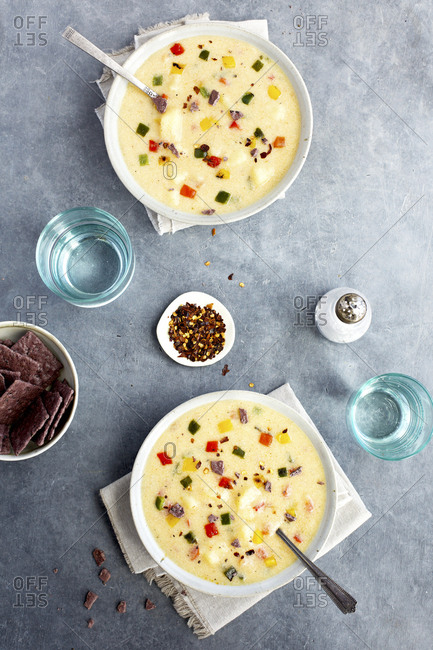 Potato Cheddar Soup with Roasted Peppers  in a bowl set on a table.