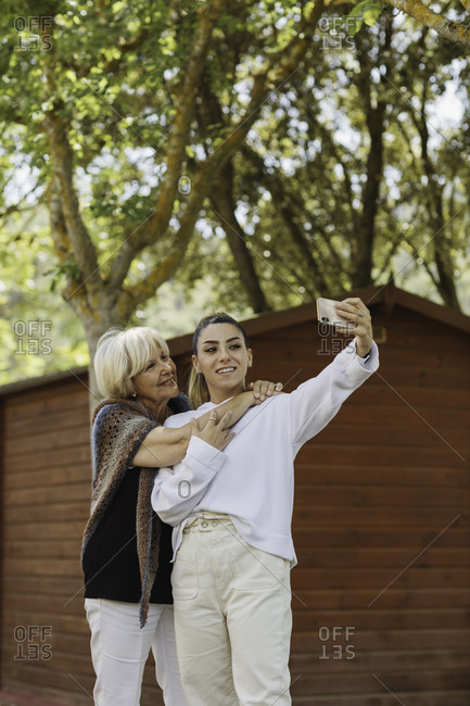 Young woman taking selfie with her grandmother