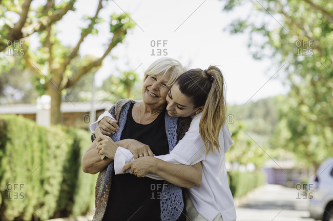 Young woman hugging her grandmother while walking in park