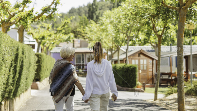 Young woman walking hand in hand in park with her grandmother