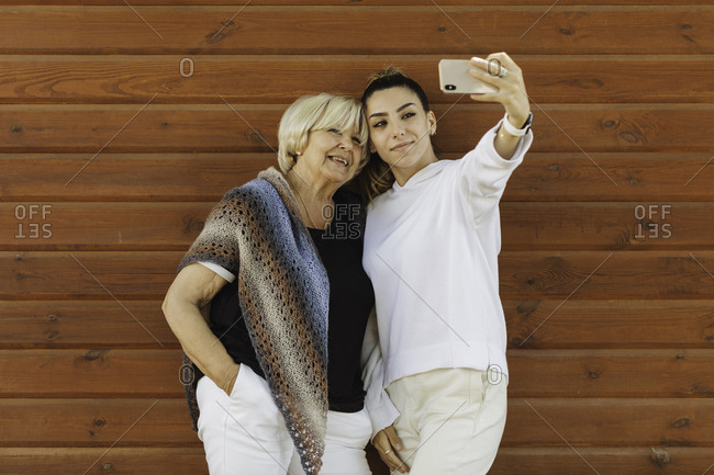 Young woman taking selfie with her grandmother in front of wood wall
