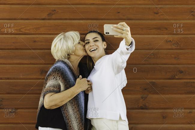 Grandmother kissing granddaughter while taking selfie