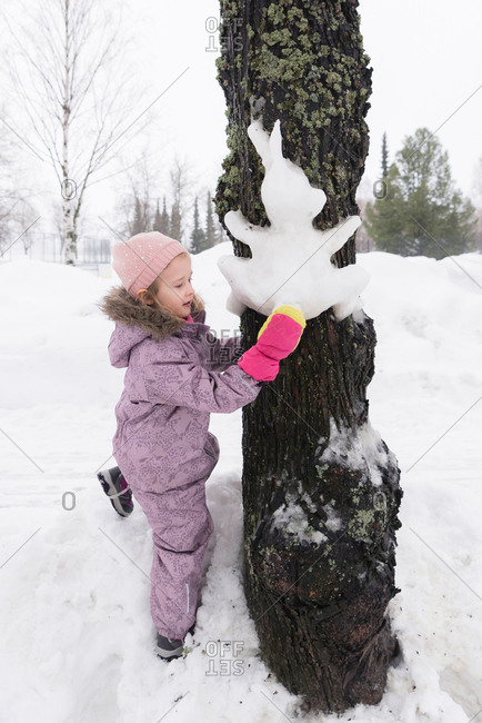 Child shaping a rabbit out of snow onto a tree