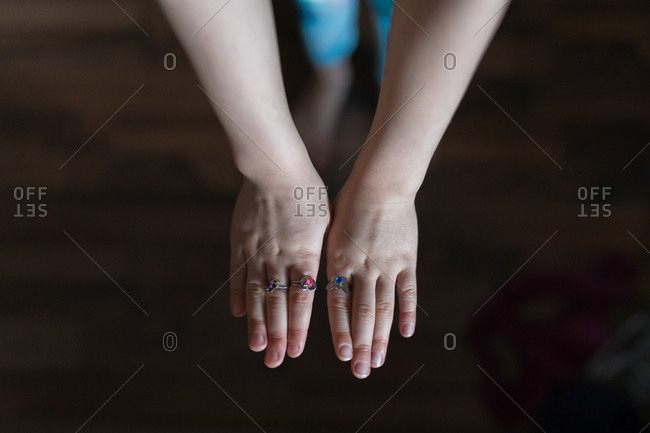 Hands of a child wearing rings