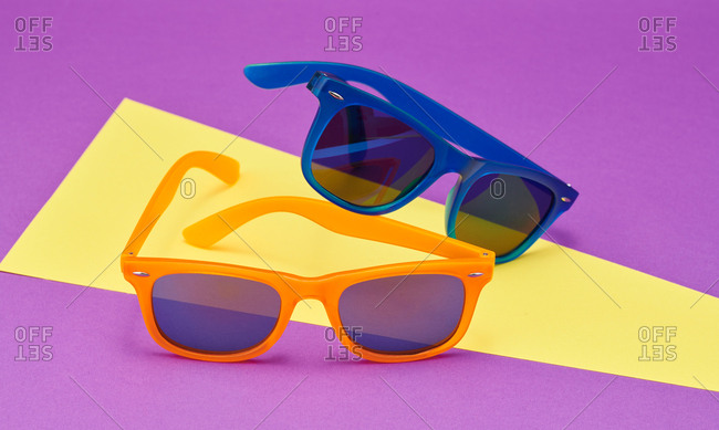 Orange and blue  sunglasses with yellow and purple abstract background
