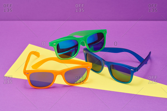 Orange, green  and blue  sunglasses with yellow and purple abstract background
