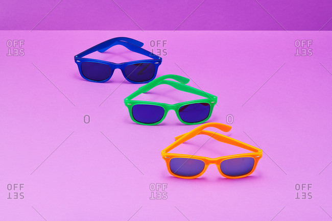 Orange, green  and blue  sunglasses purple background