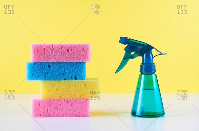 Blue spray bottle and sponges  against yellow background
