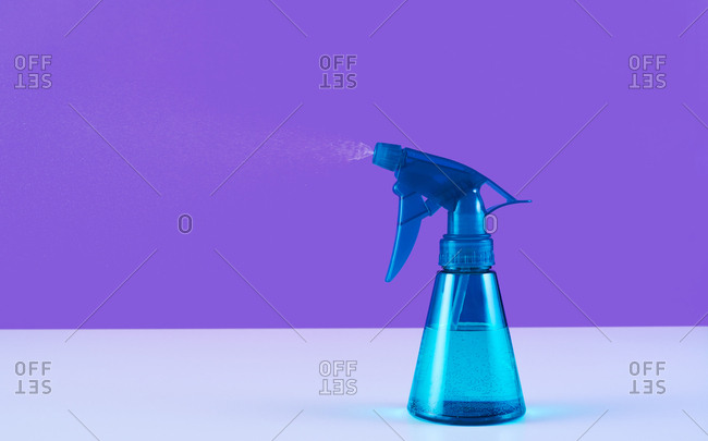 Blue spray bottle with spray against purple background