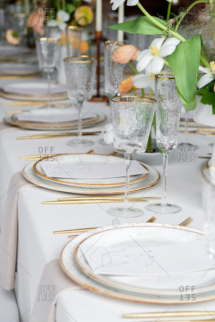 Set table at a wedding reception with gold rimmed glasses
