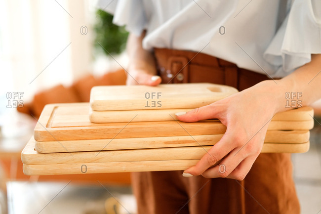 Woman carrying stack of wooden cutting boards