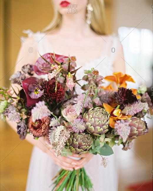 Blonde bride holding large bouquet of artichokes