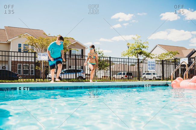 Two kids running to jump in a swimming pool