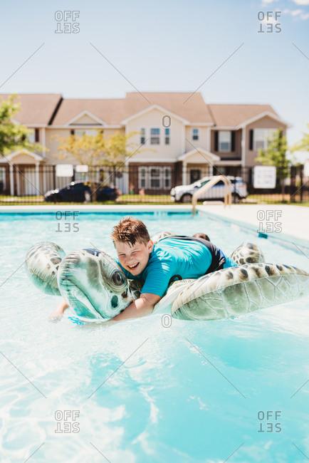 Boy in swimming pool on turtle float