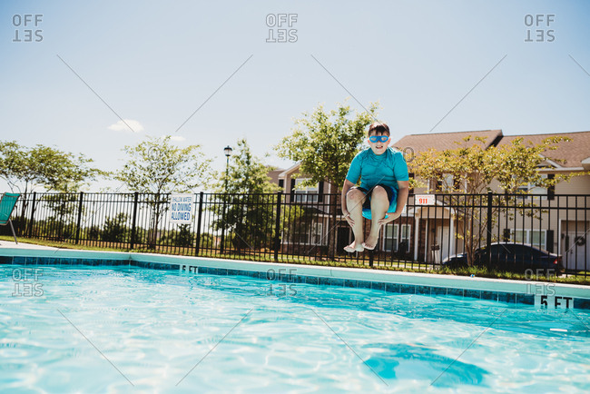 Boy doing cannon ball in swimming pool