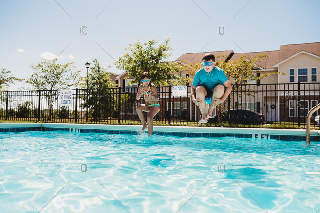 Two kids jumping into a swimming pool