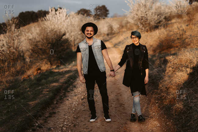Couple standing on a path holding hands