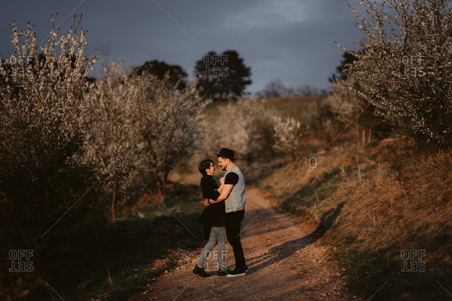 Couple embraces on a path lined with white cherry blossoms