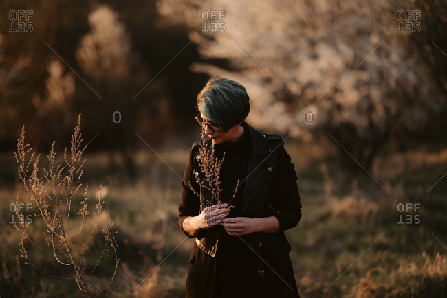 Woman admires branch of flowers