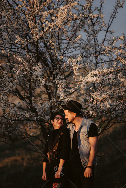 Couple smiles at each other in front of cherry blossom