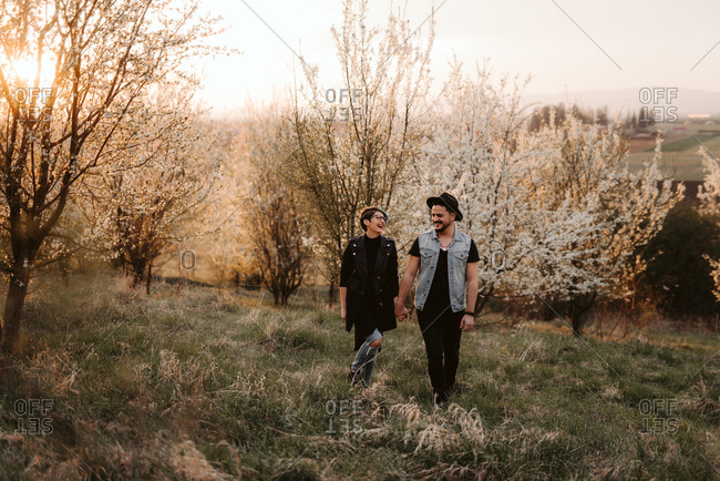 Couple walks together through cherry blossoms