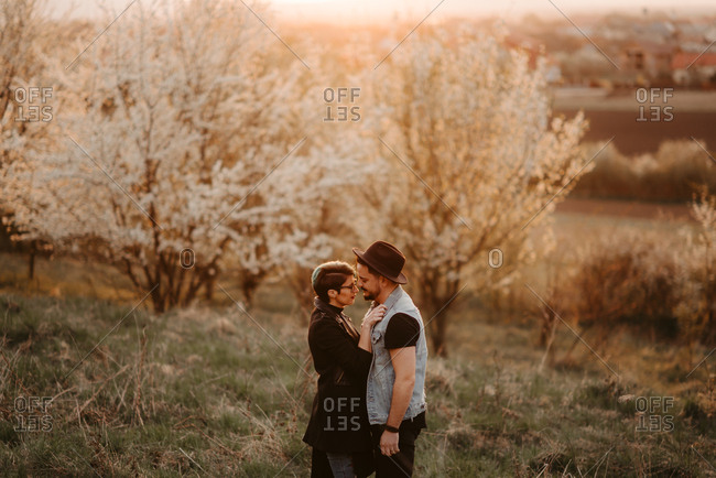 Intimate couple stands together outdoors
