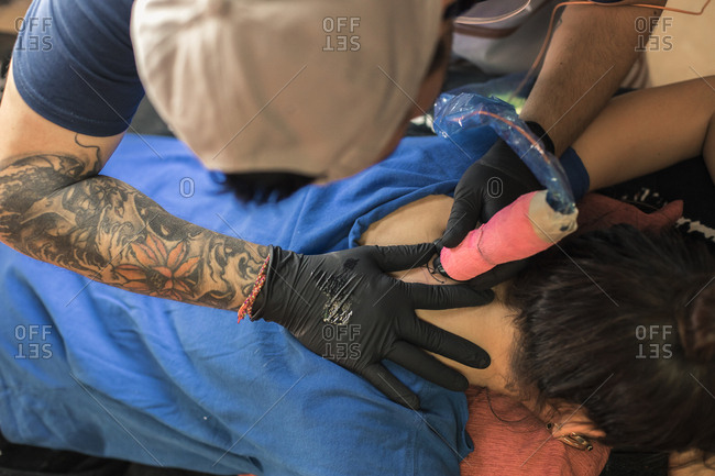 Tatto artist tattooing a woman