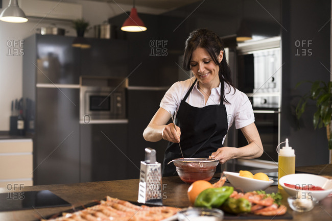 Smiling woman cooking in kitchen straining a sauce