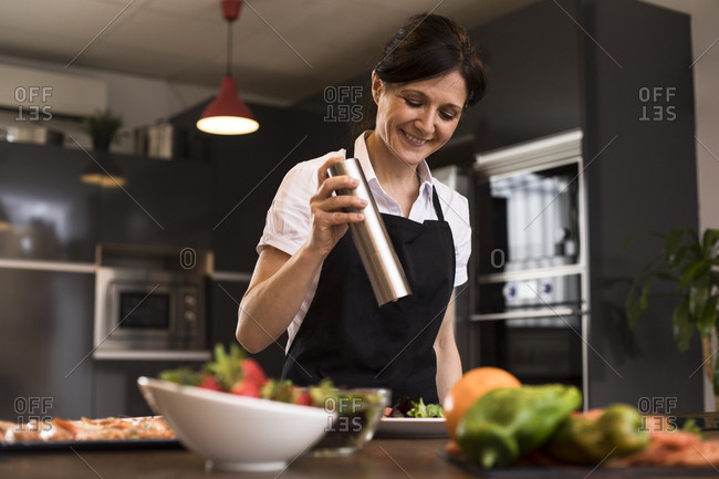 Smiling woman cooking in kitchen pouring pepper on a dish