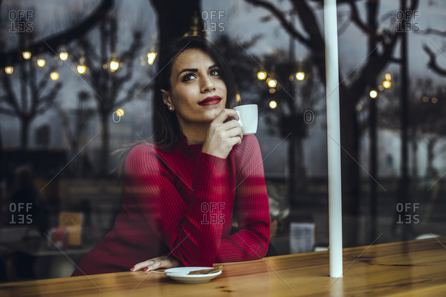 Young woman with cup of coffee behind windowpane in a cafe