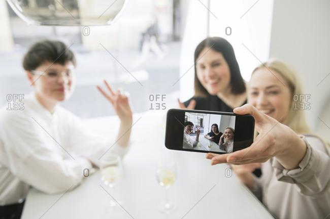 Happy friends taking selfie in a restaurant