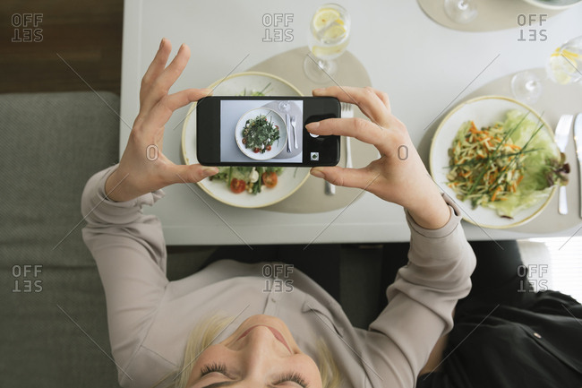 Young woman taking a cell phone picture of a salad in a restaurant