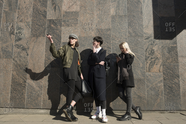 Three young women standing at a wall in the city talking