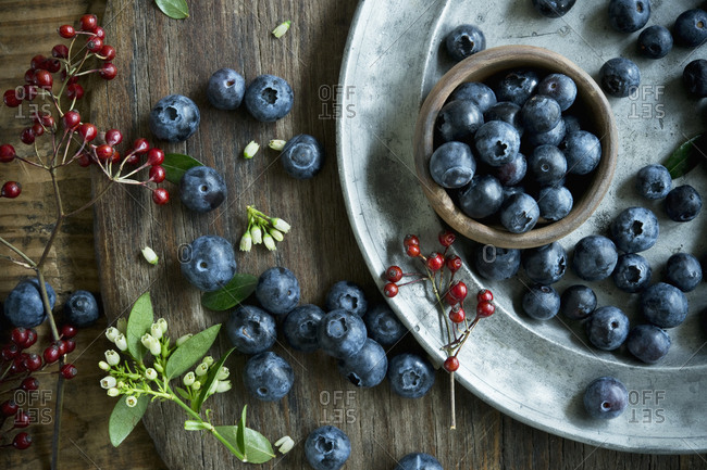 Bowl of blueberries- wooden spoon- rosehip- blueberry blossoms on wood