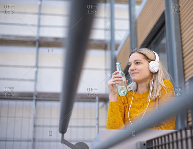 Smiling young woman with soft drink listening music with headphones