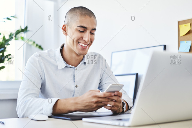 Young graphic designer sitting in home office and using smartphone