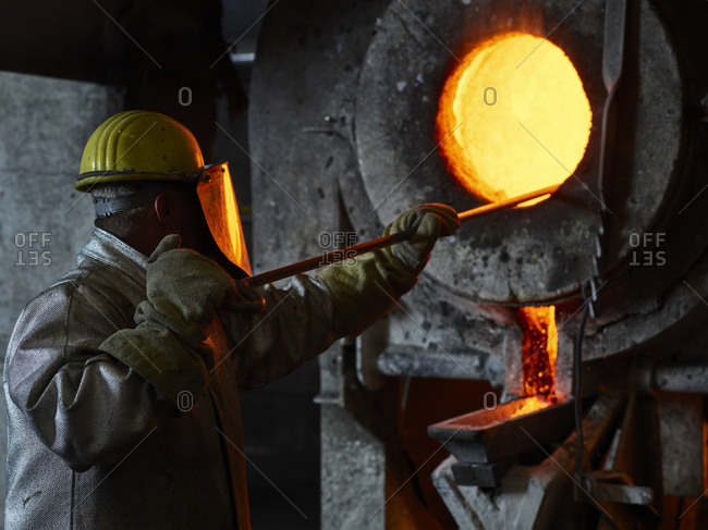 Industry- worker at furnace during melting copper- wearing a fire proximity suit