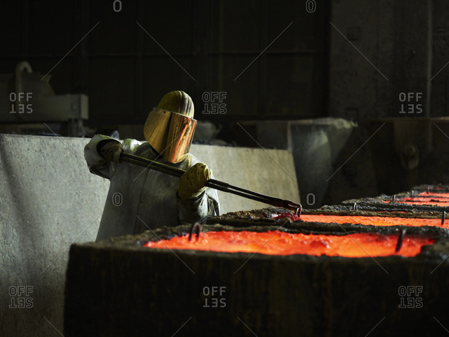 Industry- worker checking liquid copper in casting molds with pliers