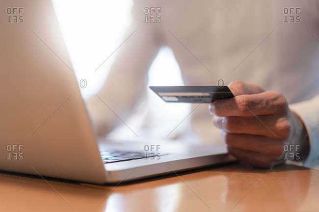 Man's hands holding credit card and while making an online payment with laptop- close-up