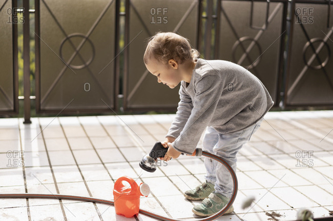 Cute little girl filling water into watering can