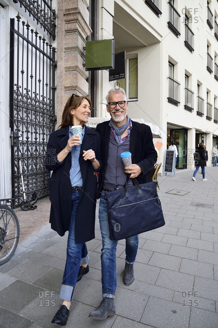 Smiling mature couple with reusable bamboo cups walking in the city