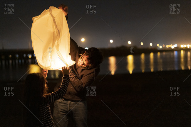Father and daughter preparing a sky lantern on the beach at night