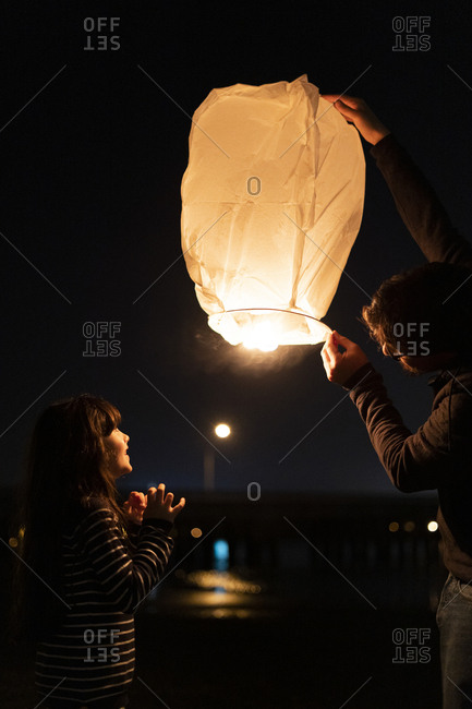 Father and daughter preparing a sky lantern at night