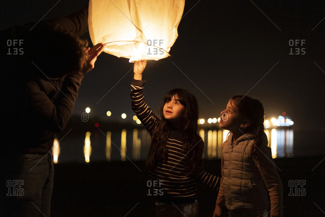 Father and two girls preparing a sky lantern on the beach at night