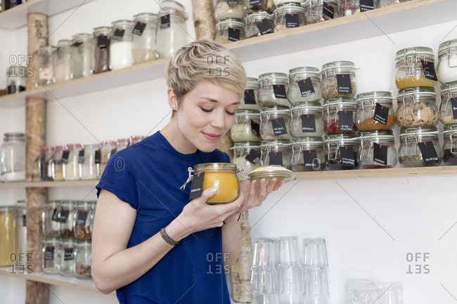 Woman smelling at jar in front of spice shelf in kitchen