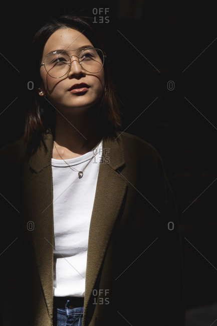 Portrait of young woman wearing glasses in sunlight looking around