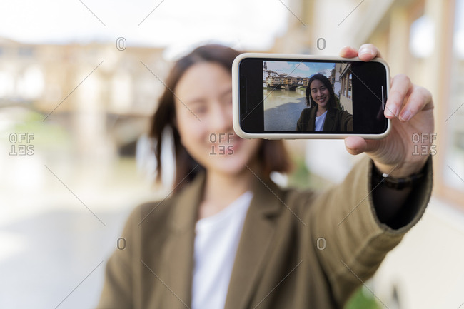 Italy- Florence- young tourist woman taking a selfie at Ponte Vecchio