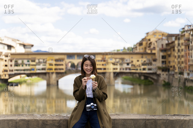 Italy- Florence- young tourist woman eating an ice cream cone at  Ponte Vecchio