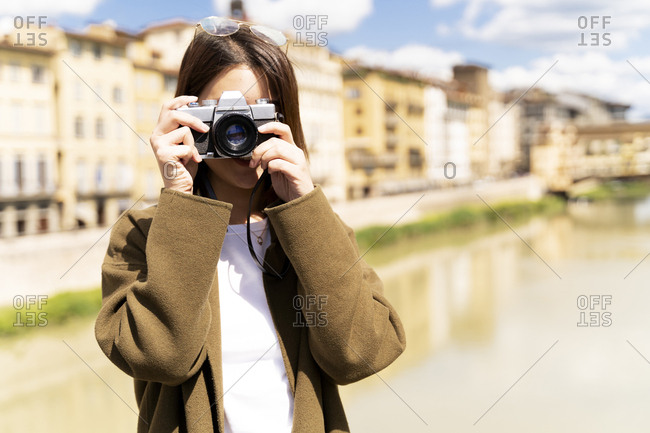 Italy- Florence- young tourist woman taking pictures at Ponte Vecchio